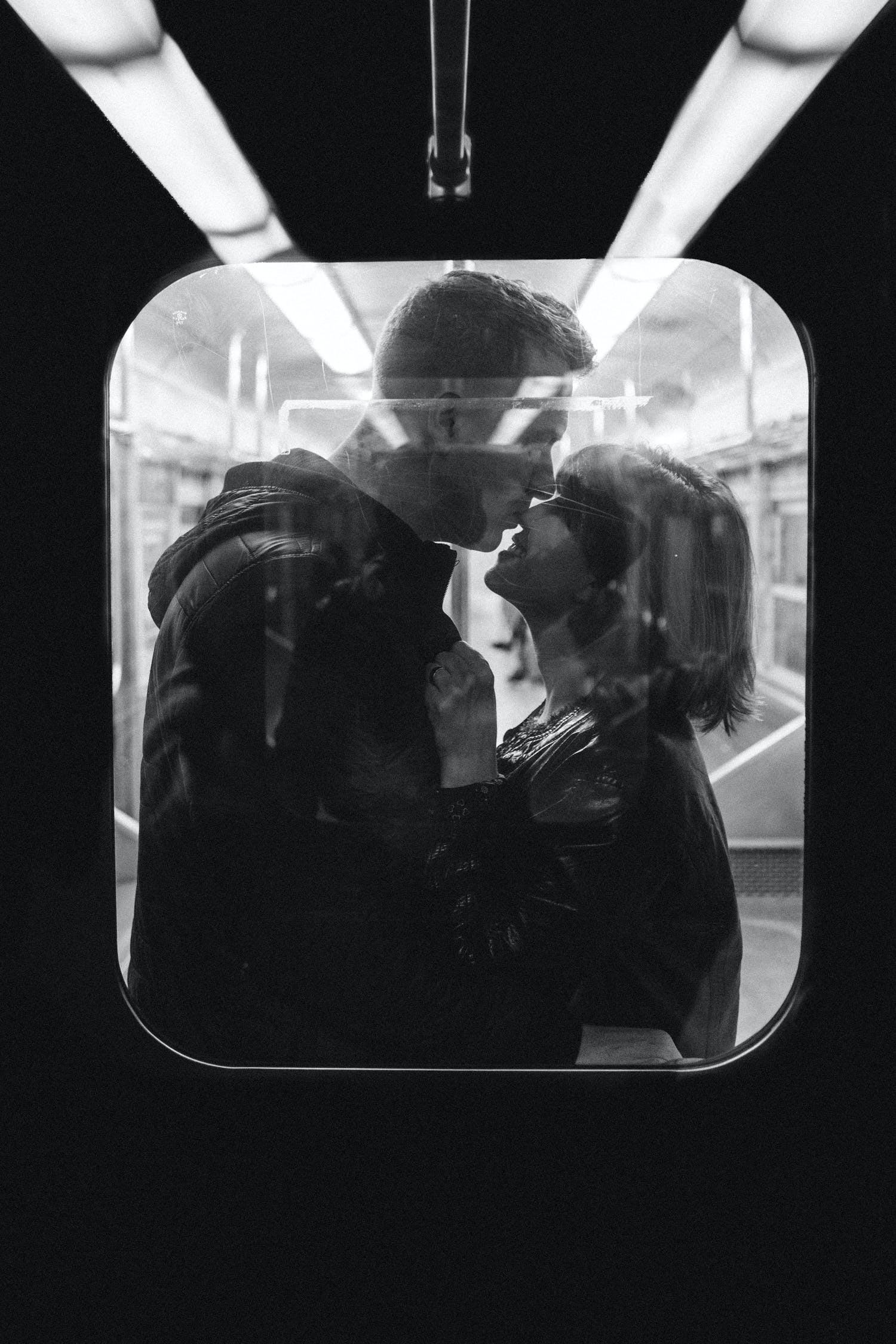 Grayscale Photo of Man Kissing Woman's Nose While Standing Inside a Train