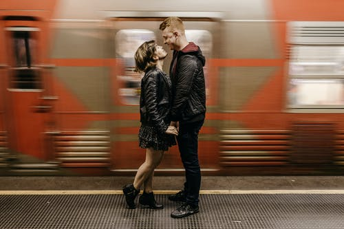 Photo of Smiling Couple Standing on Train Station Platform While Holding Hands as a Train Passes