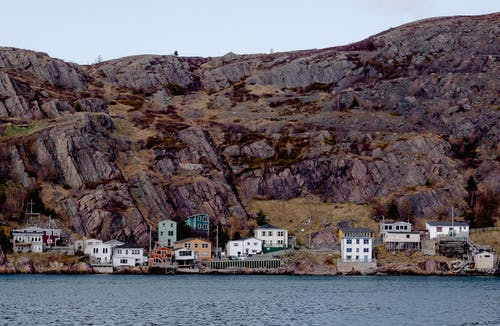 White and Gray Buildings Beside Water and Hills