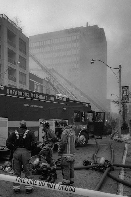 Greyscale Photography of Firemen Beside Firetruck