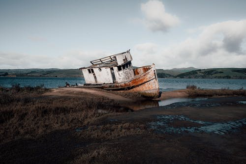 White and Rusty Boat on Seashore