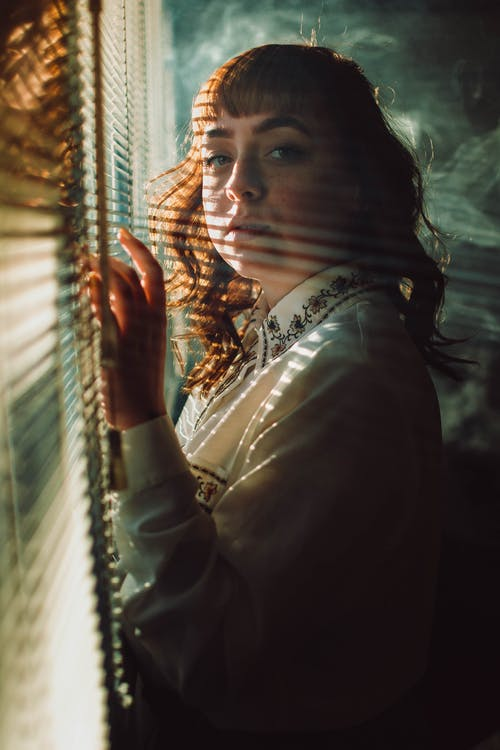 Woman Standing Beside Window