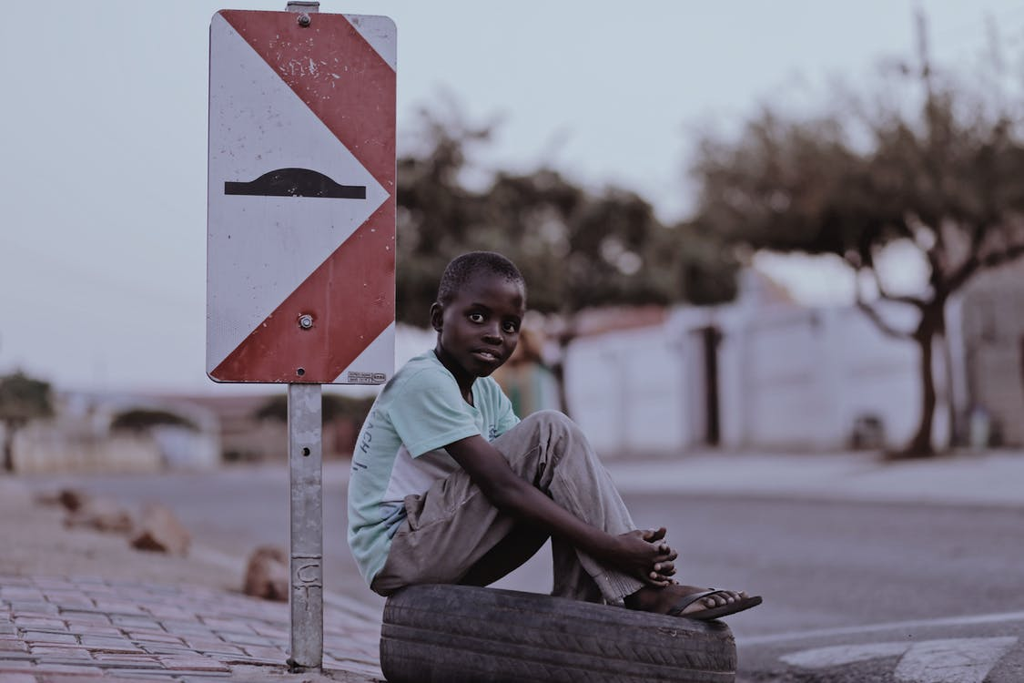 Boy Sitting on a Tire Beside Road Signage