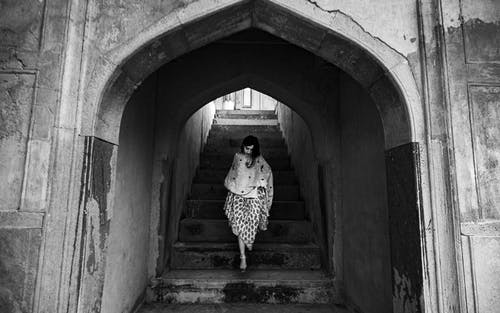 Monochrome Photo Of Woman Walking Down Stairs