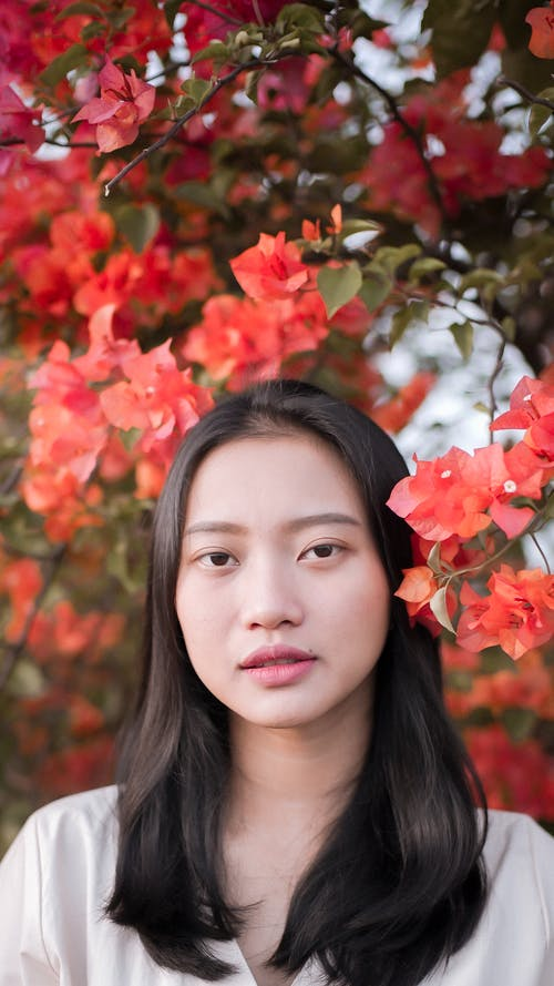Asian woman near tree with bright blooming flowers in park