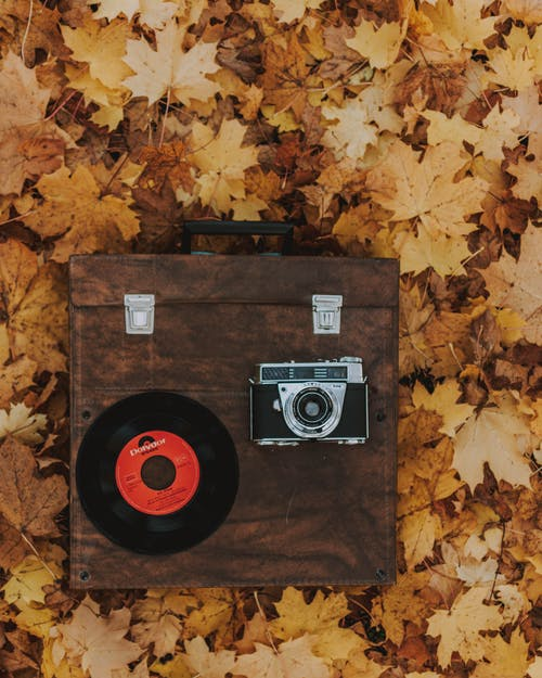 Brown Box With Black Vinyl Record and Slr Camera