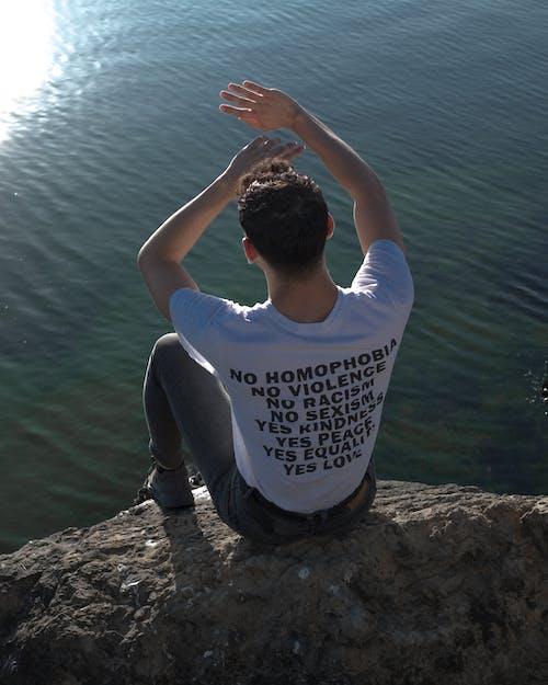 Man Wearing White T-shirt Sitting on Rock