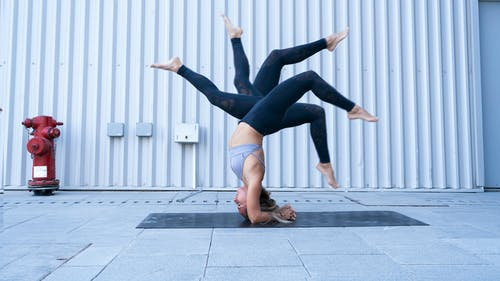 Flexible barefoot woman doing headstand pose representing various leg positions