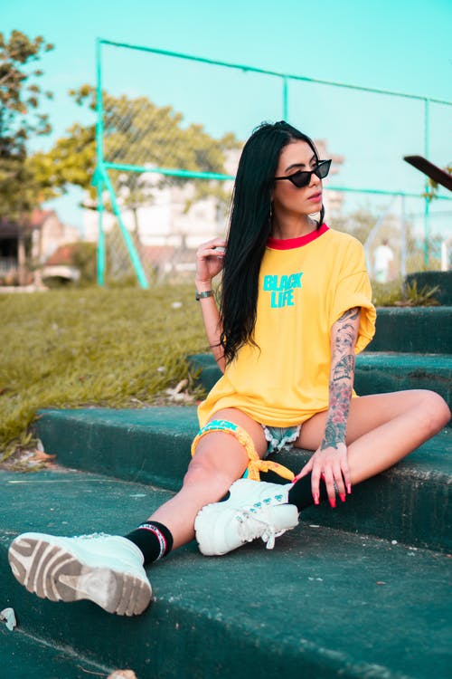 Woman in Red and Yellow T-shirt and White Sneakers