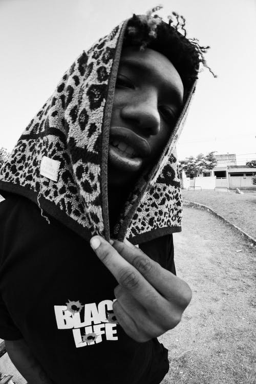 Grayscale Photo of Man Covering Head With Animal Print Towel