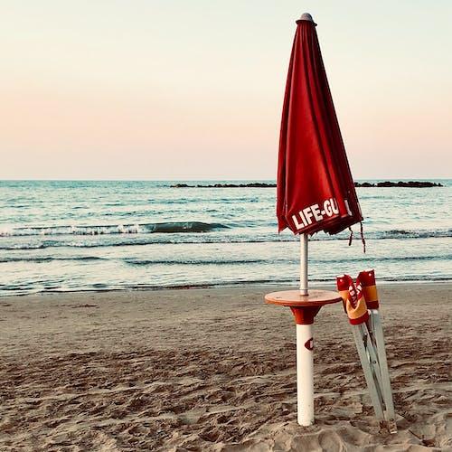 Gratis arkivbilde med kyst, livvakt, paraply, sand