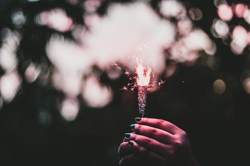 Shallow Focus Photo of Person Holding Sparkler
