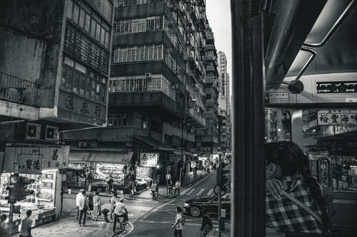 Grayscale Photography of People Walking Near High Rise Buildings