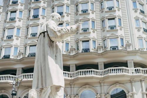 White Concrete Building With Human Statue