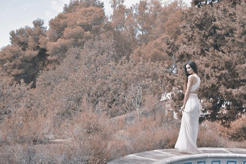 Woman Wearing White Long-Dress Standing On The Side Of  A Pool Surrounded By Trees And Shrubs