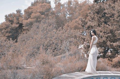 Donna Che Indossa Abito Lungo Bianco In Piedi Sul Lato Di Una Piscina Circondata Da Alberi E Arbusti