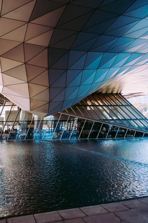 Low Angle Shot Of A Futuristic Building Design With An Outdoor Pond