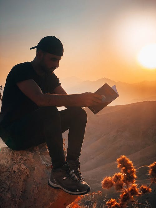 Man Sitting On A Rock Outdoors With The View Of The Mountains Reading A Book