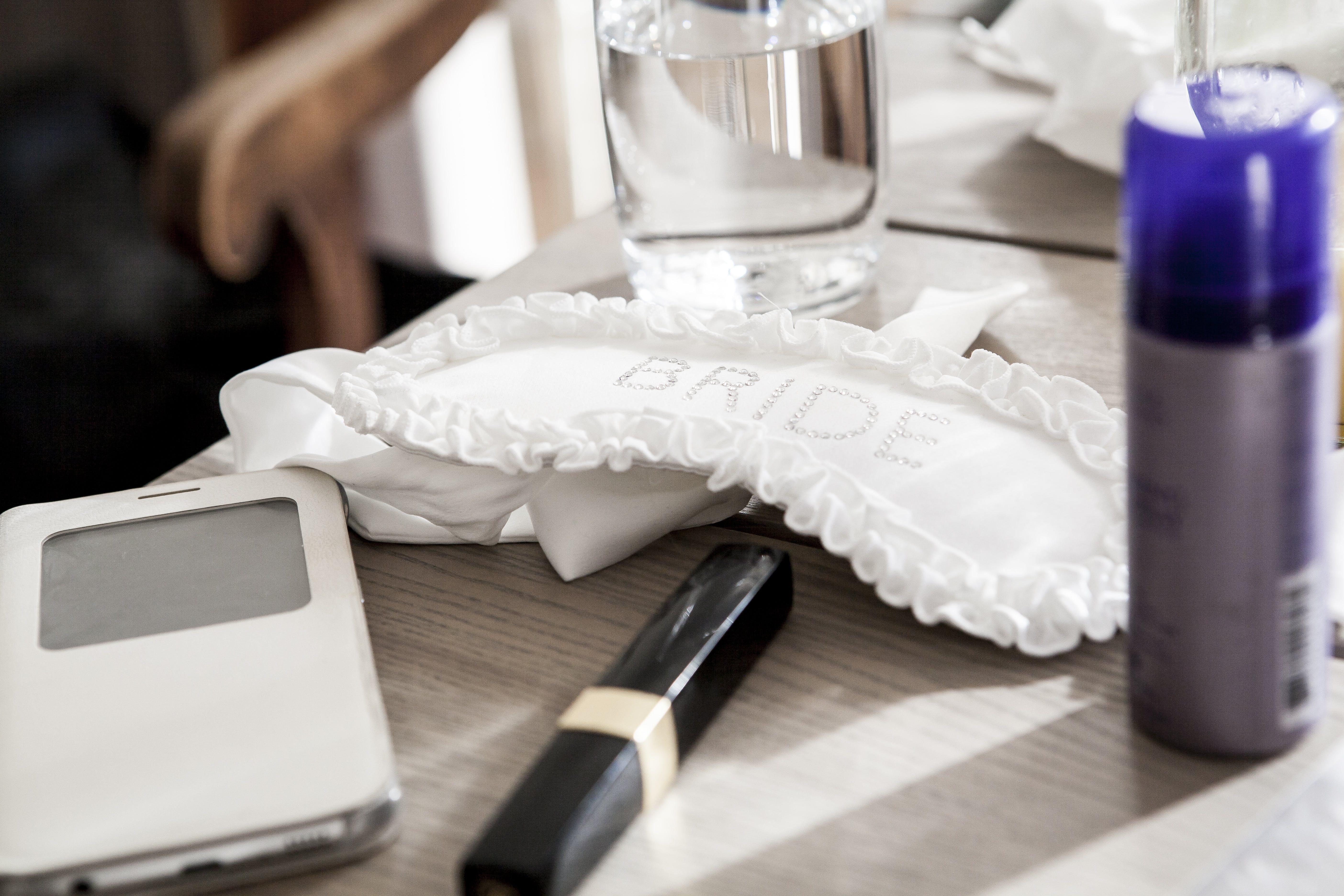 Bride Garter Beside Fragrance Bottle on Table