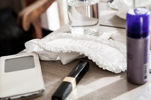 Bride Garter Beside Fragrance Bottle on Table