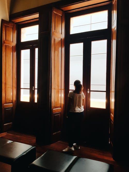 Vista Traseira De Uma Menina Em Pé Na Porta De Madeira E Vidro