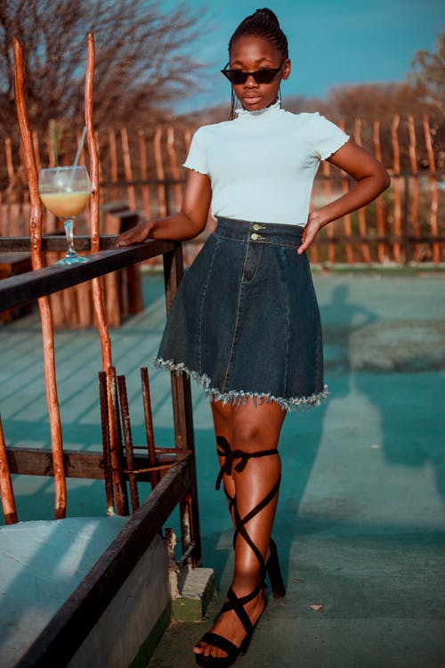 Selective Focus Photo of Standing Woman in White Shirt and Blue Denim Skirt Posing by Wooden Railing