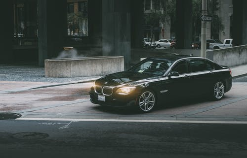 Black Bmw Sedan Beside Concrete Curb