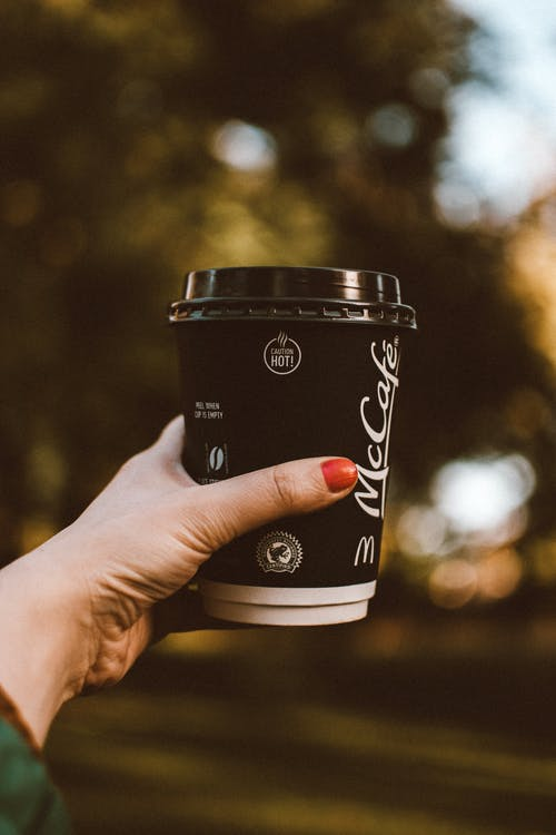 Selective Focus Photo of Woman's Hand Holding Out a McCafe Cup of Coffee