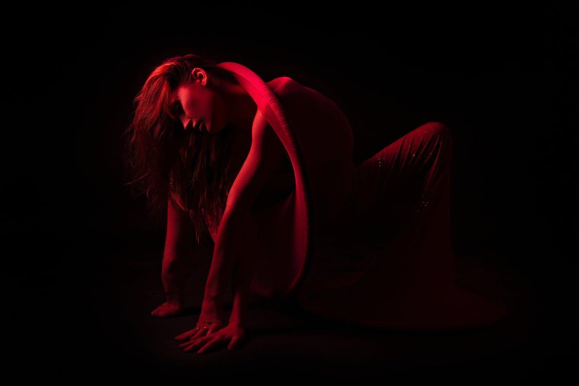 Bending Woman in Dark Room