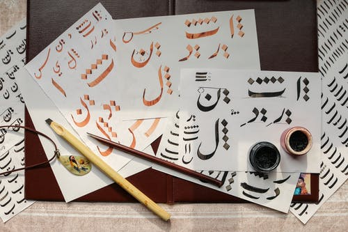 White Papers on Table with Written Calligraphy Art