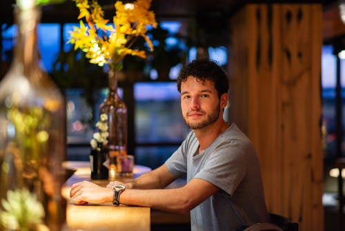 Man in Gray Crew-neck Shirt Sitting Indoors