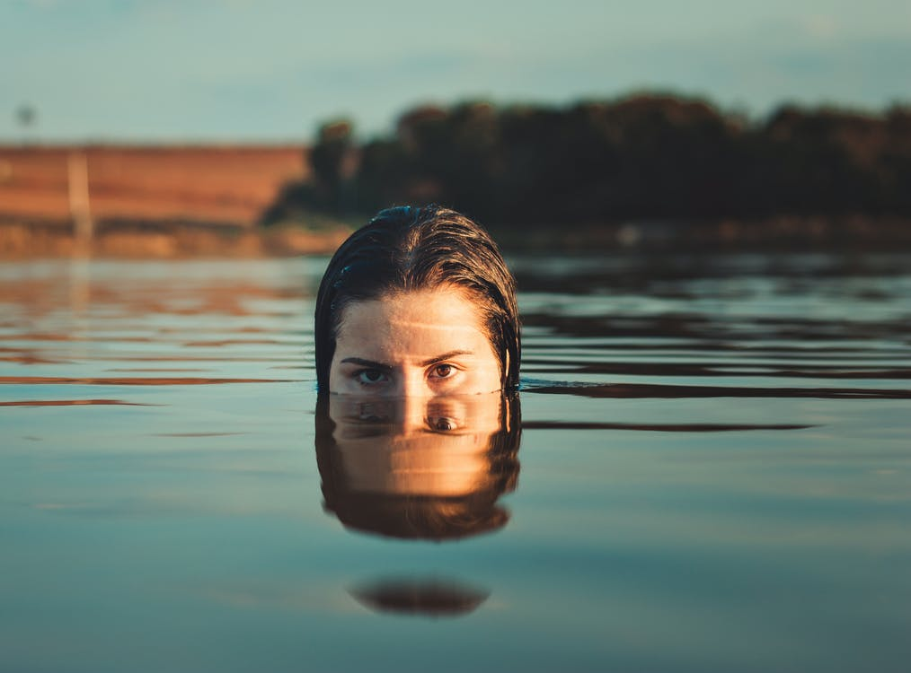 Woman Sticking Half of Her Face Out of Body of Water