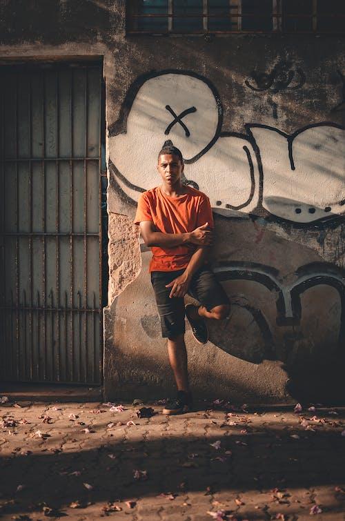Man Leans on Graffiti Wall