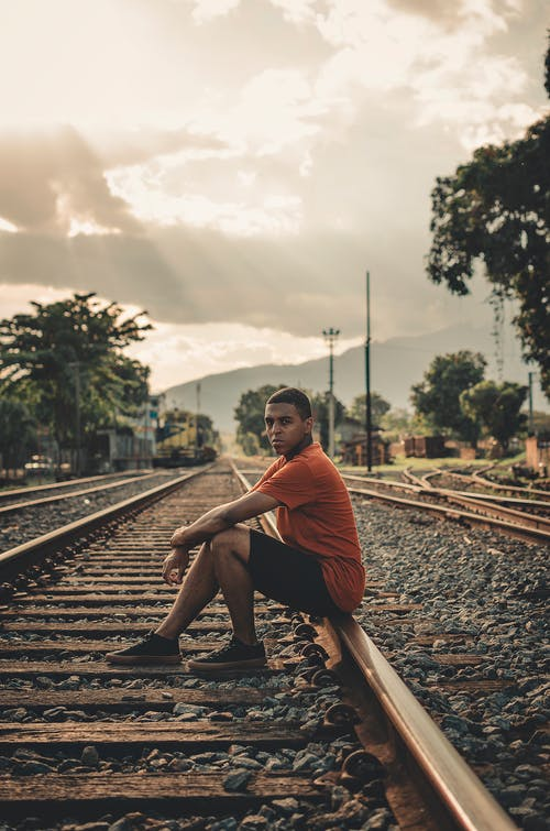 Man Sitting on Railroad during Day