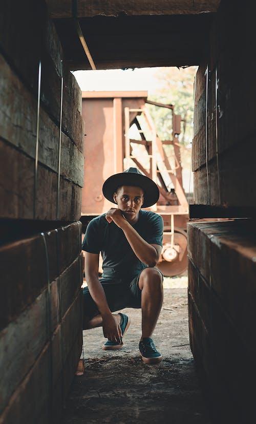 Man Sitting Near Brown Wall