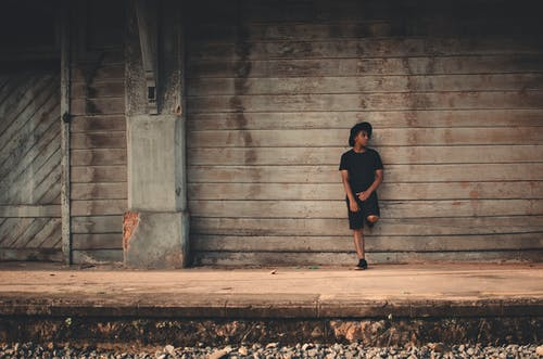 Photo of Man in Black T-shirt, Shorts, and Fedora Leaning on Wooden Wall Posing While Looking Away