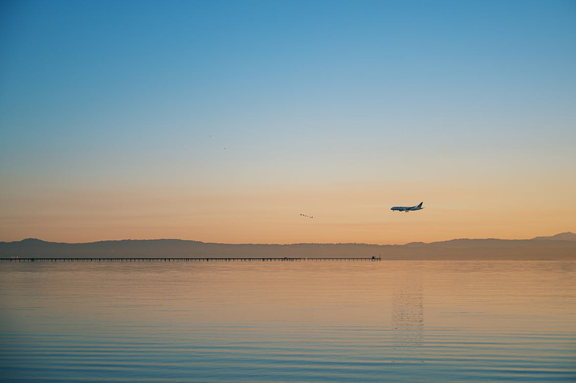 Airplane Flying over Body of Water