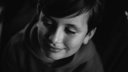 Grayscale Photo of Smiling Boy In a Dark Room Looking Away
