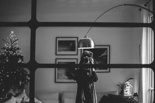 Grayscale Photography of Person Taking Photo Under the Floor Lamp