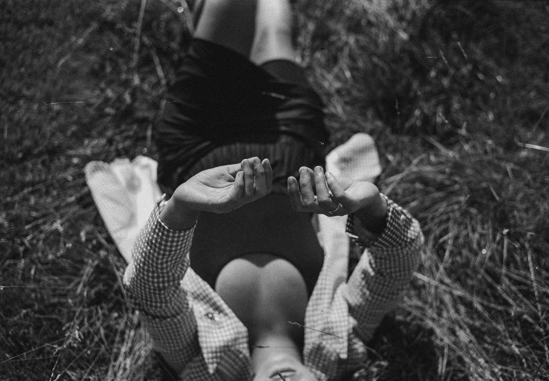 Grayscale Photography of Person Lying on Grass