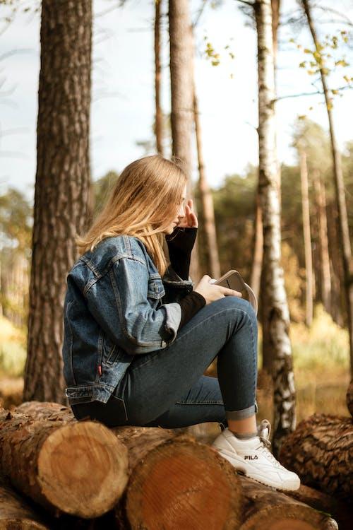 Woman Sitting on Wood Logs