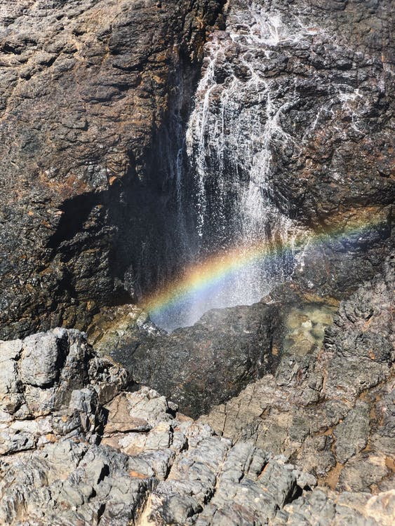 Rainbow Reflection on Water Flowing over Rock