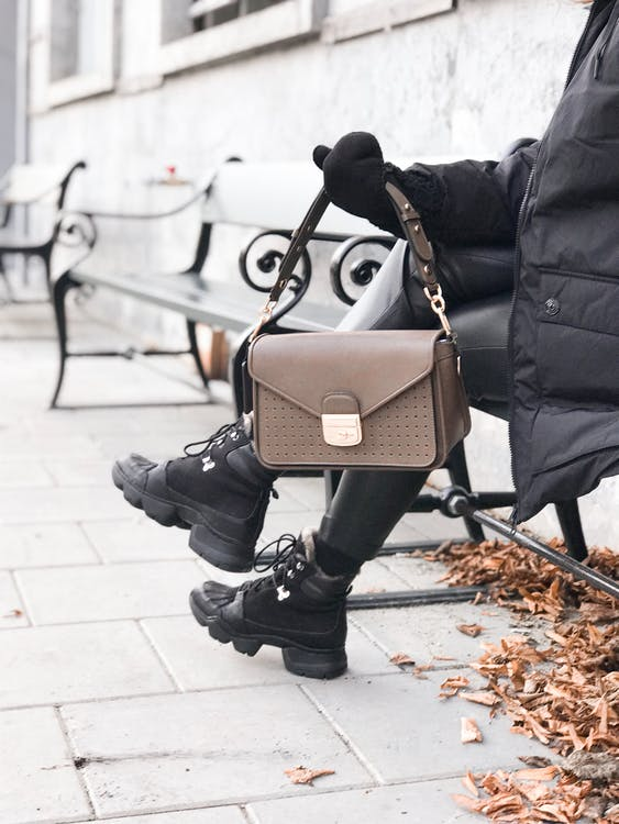Faceless woman showing trendy hand bag while resting on bench