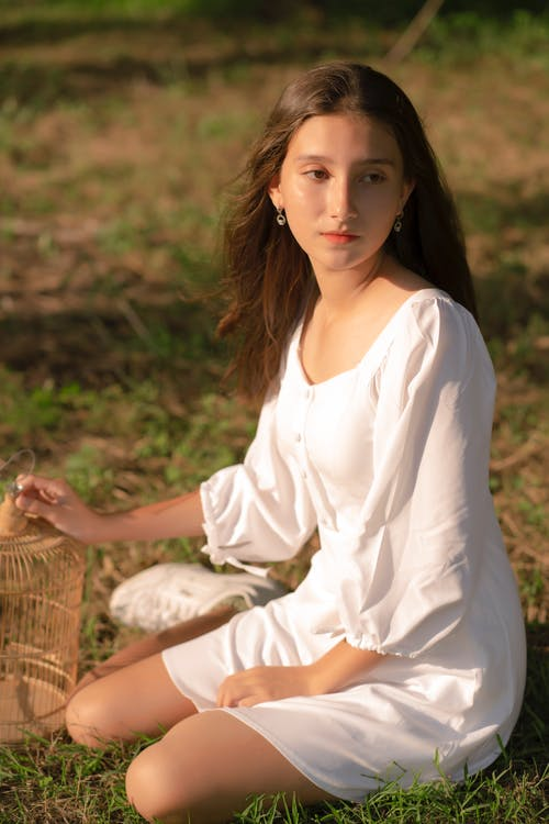 Contemplative teenager resting on grass in countryside