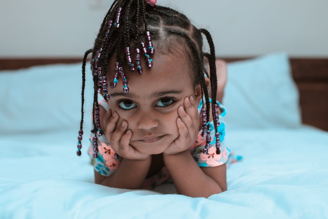 Selective Focus Photo of Little Girl Lying Forward on the Bed