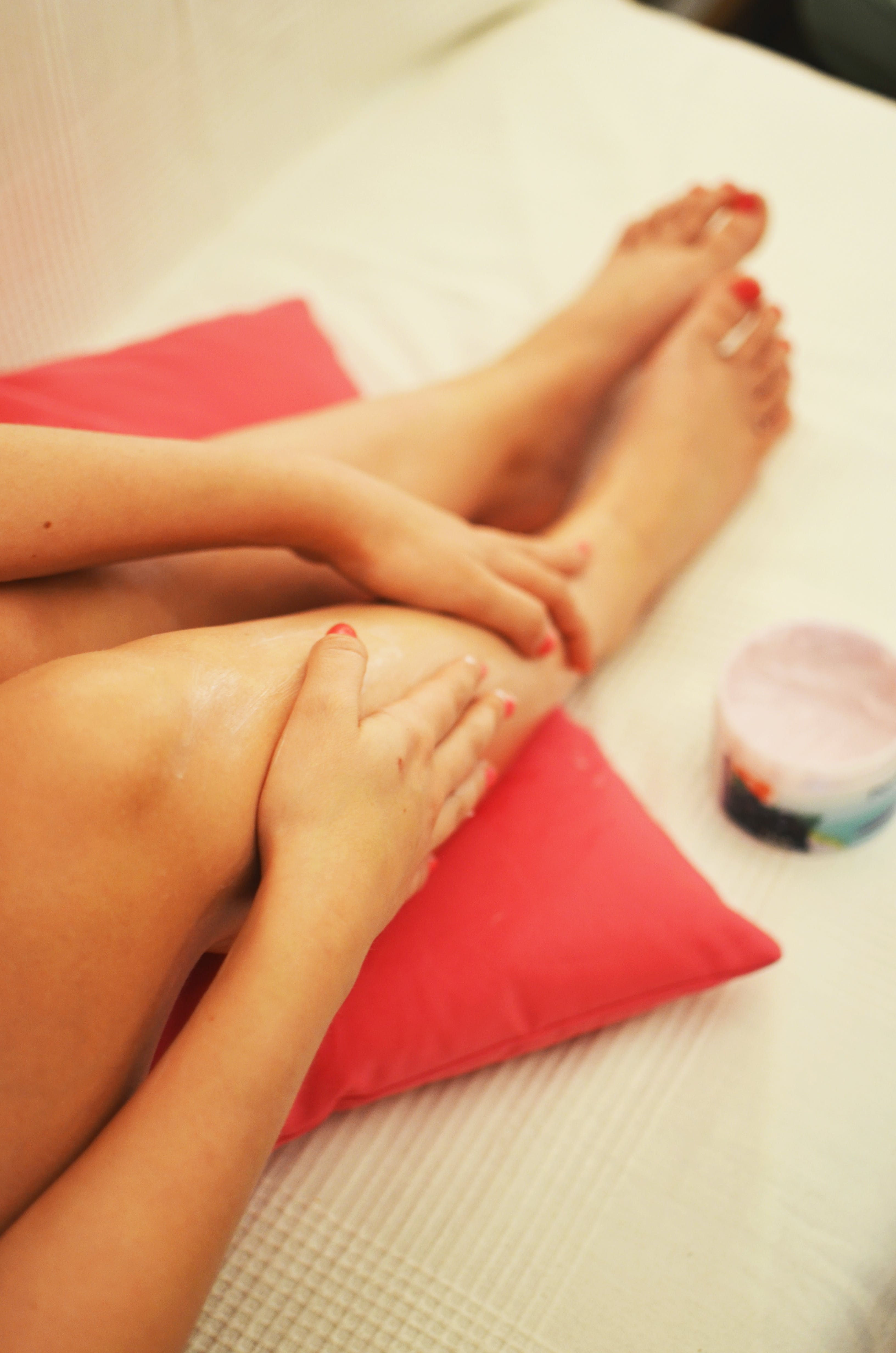 This photo shows the legs of a woman who is sitting on a red pillow on a pastel colored couch. The woman is putting on some lotion on her legs with her hands. She has red toenails. Thew whole setting makes a very relaxing impression.