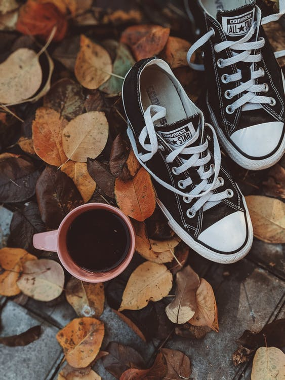 High Angle Photo of Converse All Star Sneakers Near Cup of Coffee