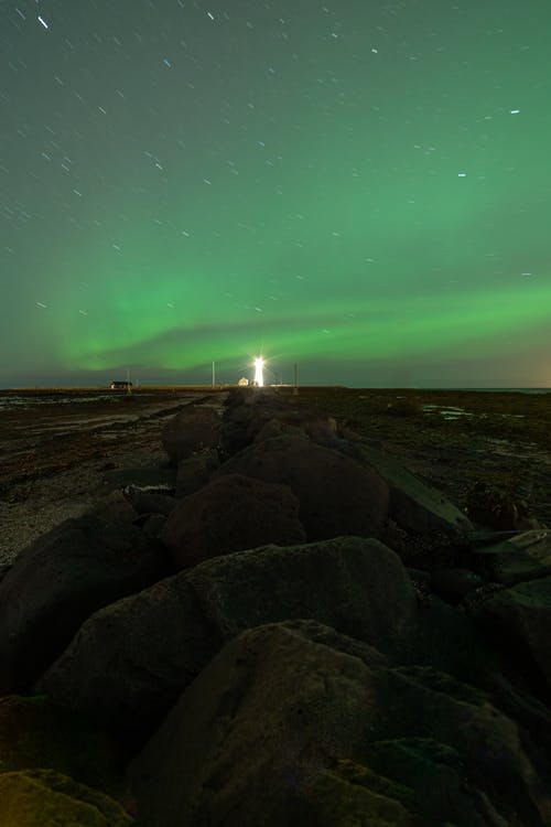 Bright northern lights and lighthouse under sky at night