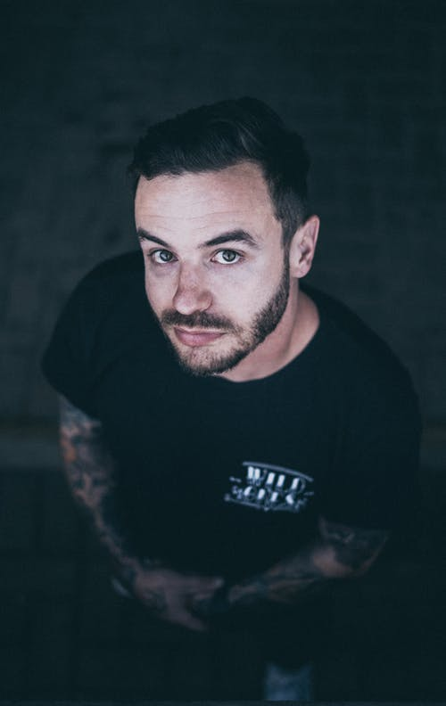 Selective Focus Photo of Tattooed Man in Black T-shirt Posing While Looking Up