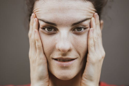Selective Focus Portrait Photo of Woman Stretching Face